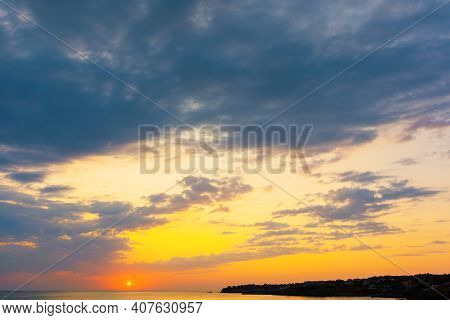 Dynamic Cloudscape In Summer At Sunrise. Dark Clouds On The Sky In Yellow And Pink Morning Light. Dr