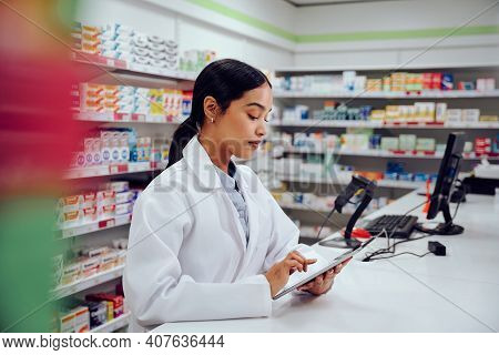 Young Female Pharmacist Standing Behind Counter Wearing Labcoat Using Digital Tablet In Chemist