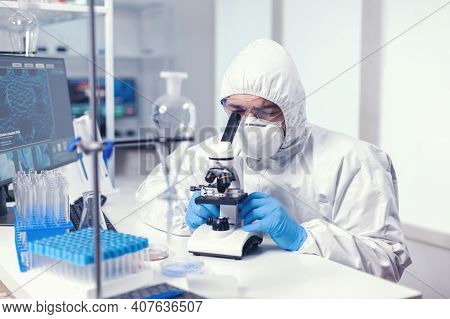 Analyzing Virus In Microbiology Lab Using Microscope Wearing Ppe Suit And Glasses. Virolog In Covera