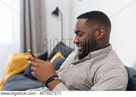 Attractive Millennial Young African American Man Relaxing And Sitting On The Sofa, Typing A Message,