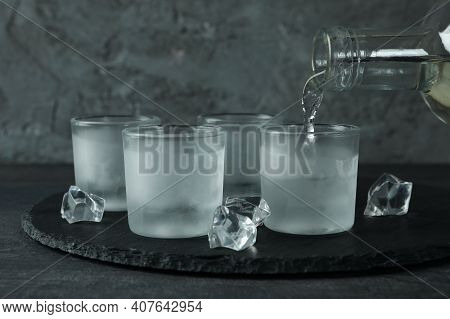 A Bottle With Pouring Vodka And Shots Of Vodka On Black Tray
