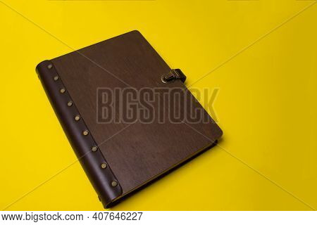 Family Photo Book On Yellow Background. Brown Photo Book With Dark Wood Cover. Wedding Photo Album.