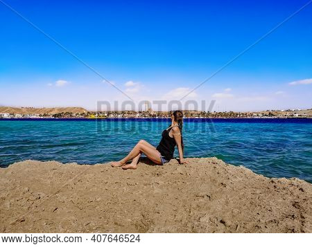 Young Woman Sits On A Rock Against The Backdrop Of A Panorama Of Sharm El Maya Bay In Sharm El Sheik