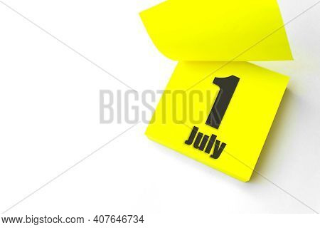July 1st . Day 1 Of Month, Calendar Date. Close-up Blank Yellow Paper Reminder Sticky Note On White