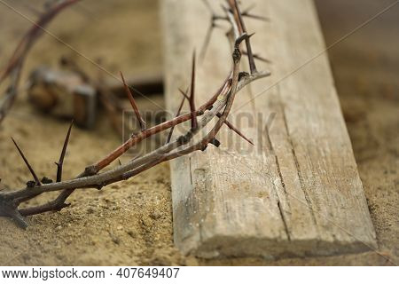 Crown Of Thorns And Wooden Plank On Sand, Closeup. Easter Attribute
