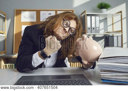 Angry Broke Man Sitting At Office Desk And Threatening Piggy Bank With Clenched Fist