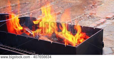 An Open Fire Was Lit In The Barbecue For Frying Meat And Vegetables. Flaming Log Tree In A Metal Str