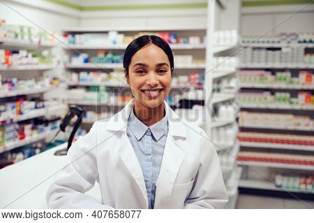 Happy Successful Woman Working In A Pharmacy Wearing Labcoat Smiling At Camera