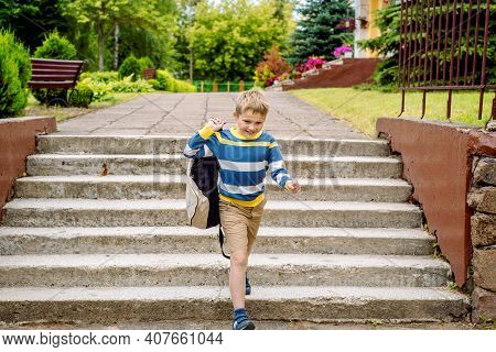 Portrait Of A Schoolchild With Backpack Leaping . The Boy Runs A Backpack Around The School Yard.chi