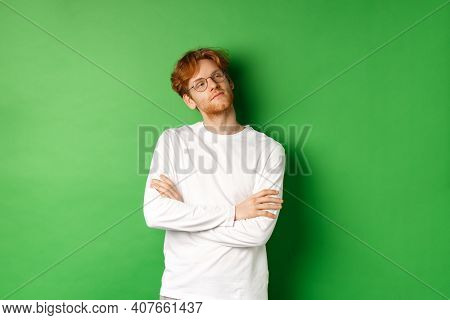 Confident Young Man With Red Hair, Wearing Glasses, Looking Smug At Right Side Copy Space, Cross Arm