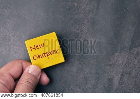 Top View Of Man Hand Holding Yellow Board Written With Text New Chapter