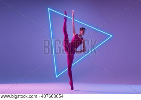 Young And Graceful Ballet Dancer Isolated On Purple Studio Background In Neon Light With Glowing Tri