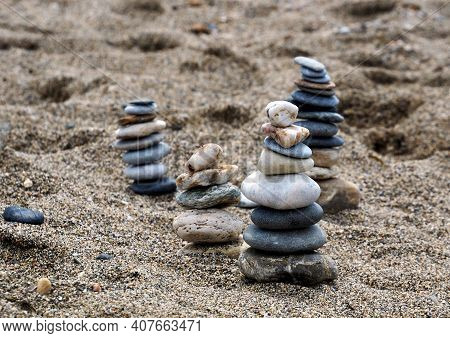 Pyramids Of Small Stones Rise Above The Sand. Flat And Oval Pebbles Are Stacked On Top Of Each Other
