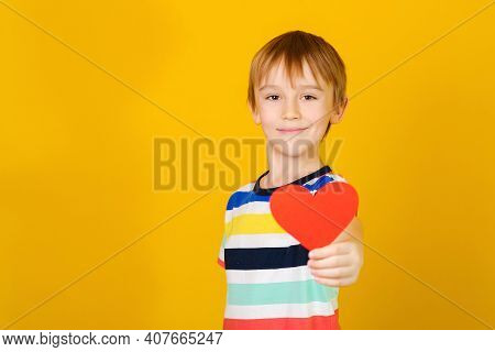 Happy Child With Red Heart Over Yellow Backgound. Holidays Concept.