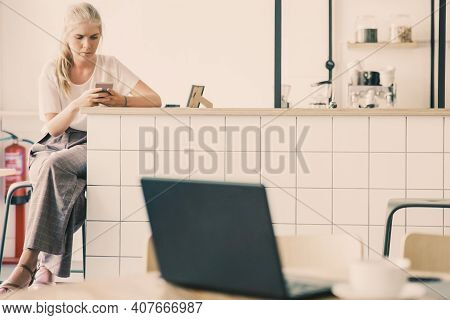 Focused Beautiful Blonde Woman Using Smartphone, Sitting At Kitchen Counter In Co-working Space. Can