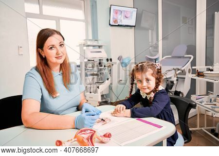 Girl Studying Female Reproductive System With Doctor In Gynecological Cabinet. Gynecologist And Cute
