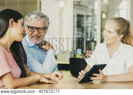 Cheerful Female Consultant And Young And Mature Customers Watching And Discussing Presentation On Ta