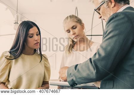 Serious Male Inspector With Notepad Meeting And Discussing Papers With Young Entrepreneurs. Business