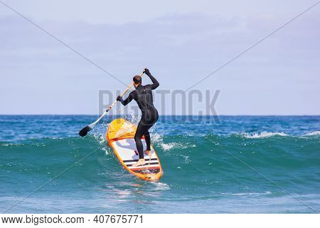 Man Surfing On Inflatable Stand-up Paddle Board At Summer Sunny Day. Extreme Sport Activity. Surfer