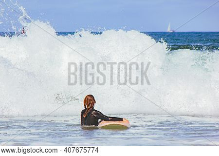 Unrecognizable Woman With Surfboard Going Into The Sea With Big Waves. Woman With Wetsuit Surfboardi