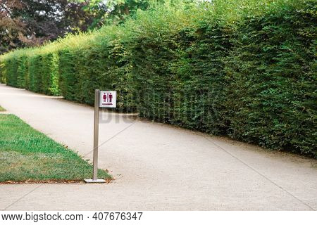 Signpost For Mens And Womens Restrooms In Park Near Trimmed Tall Green Bush