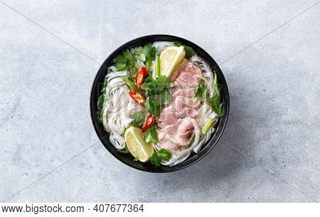 Pho Bo Vietnamese Soup With Beef And Rice Noodles On A Concrete Background, Top View