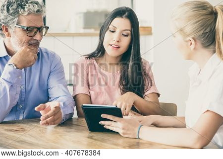 Female Consultant Or Manager Meeting With Couple Of Young And Mature Customers, Presenting Content O