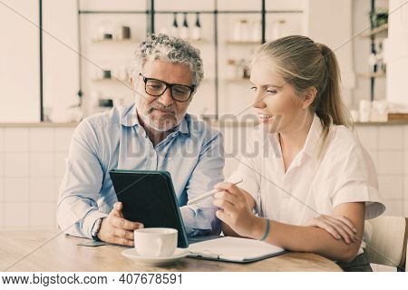 Positive Mature Male Mentor Explaining Work Details To Intern. Business Man Showing Tablet Screen To