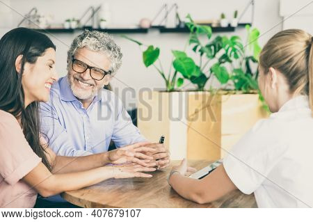 Happy Couple Of Young And Mature Customers Meeting With Agent, Watching And Discussing Presentation