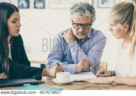 Family Legal Advisor Explaining Document Details To Mature Father And Adult Daughter. Medium Shot. E
