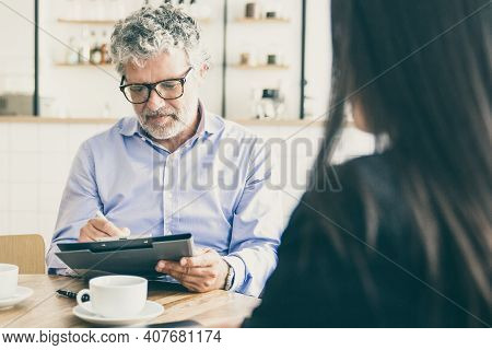 Focused Mature Businessman Meeting With Agent Over Cup Of Coffee At Wo-working Female And Signing Ag