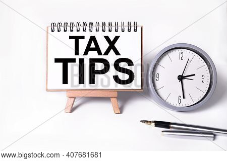 Tax Tips. Text On White Notepad Paper On White Background. Near The Table Clock
