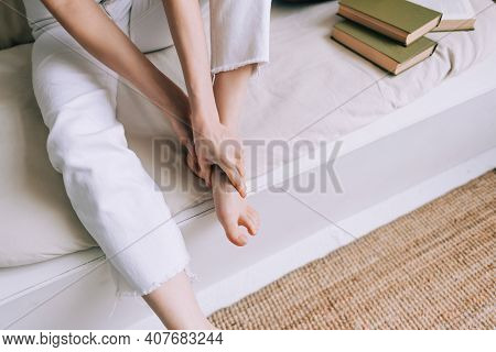 Woman Sitting On The Bed Massages Her Foot, Close-up. Woman With A Slender Body Massages The Leg, Yo