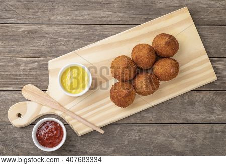 Typical Brazilian Snack Coxinha On A Board Over Wooden Table..