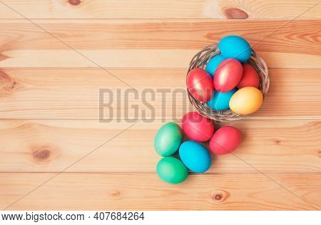 Colorful Easter Eggs In Wicker Basket On Wooden Background.  Top View With Copy Space.