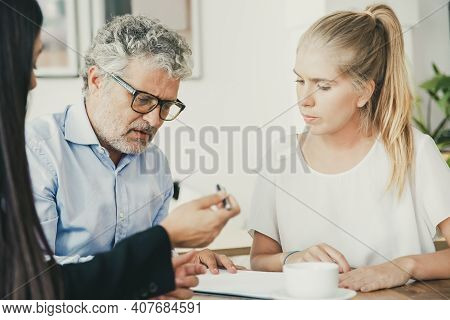 Focused Mature Man Reading Document, His Female Colleague Giving Pen To Him For Signing. Medium Shot
