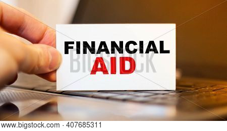 Man Holding Paper With Financial Aid On Background Of Office Computer
