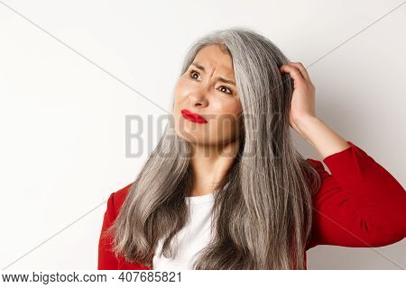 Close Up Of Complicated Asian Mature Woman Scratching Head, Looking Confused At Upper Left Corner, S
