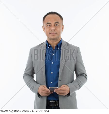 Middle Age Asian Man Wearing A Grey Jacket With Informal Casual Style And Holding A Smartphone In Ha