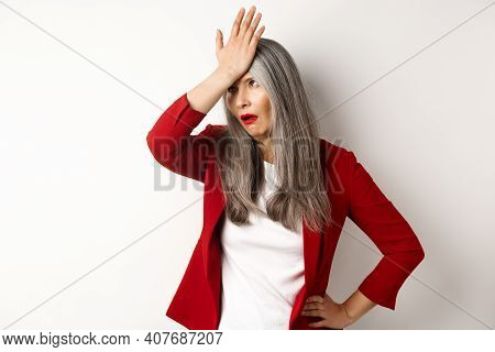 Annoyed Asian Office Lady In Red Blazer Roll Eyes And Facepalm, Standing Bothered And Irritated Over