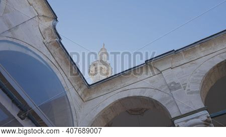 Tower And Arches Of Mosque On Background Of Blue Sky. Action. Bottom View Of Beautiful Parts Of Arch