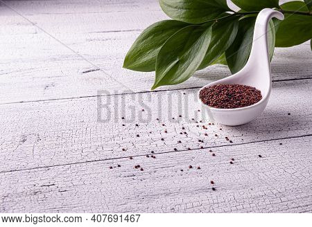 Red Raw Quinoa Seeds In White Spoon Bowl On White Textured Wooden Table. Few Seeds Are Scattered Aro