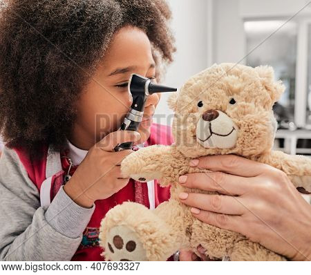 African American Girl Plays With Her Toy Bear In A Medical Game, Using An Otoscope. Hearing Clinic F