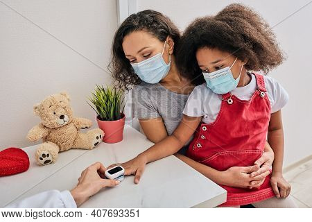 Measurement Of Oxygen Saturation And Pulse Of A Child. African American Little Girl And Her Mom Wear