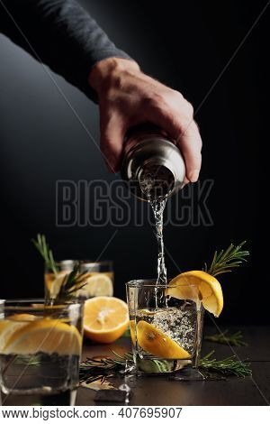 Cocktail Gin And Tonic With Lemon And Rosemary. The Bartender Pours A Cocktail From A Shaker Into A