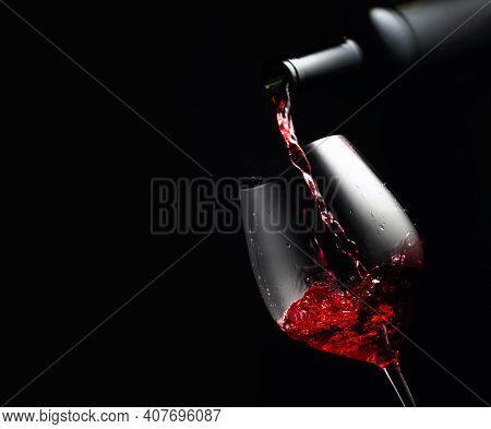 Pouring Red Wine In A Glass Goblet. Black Background With Copy Space.