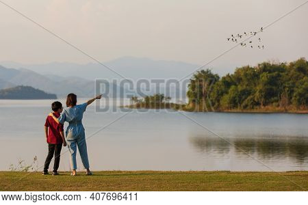 Mother And Son Standing Beside Big Lake And See Mountain View In The Background, Mom Pointing Finger