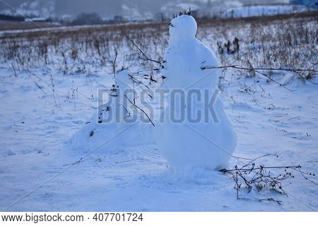 Two Snowmen Stand On A Meadow In A Village Traditional With Branches
