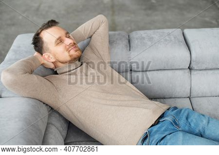 Handsome Smiling Guy Take A Nap Lying On The Comfortable Sofa With Eyes Closed And Hands Behind Head