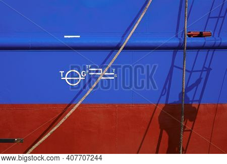 Shadow Of Worker On Ladder Is Painting Rust Proof Color With White Plimsoll Mark On Blue And Red Ste